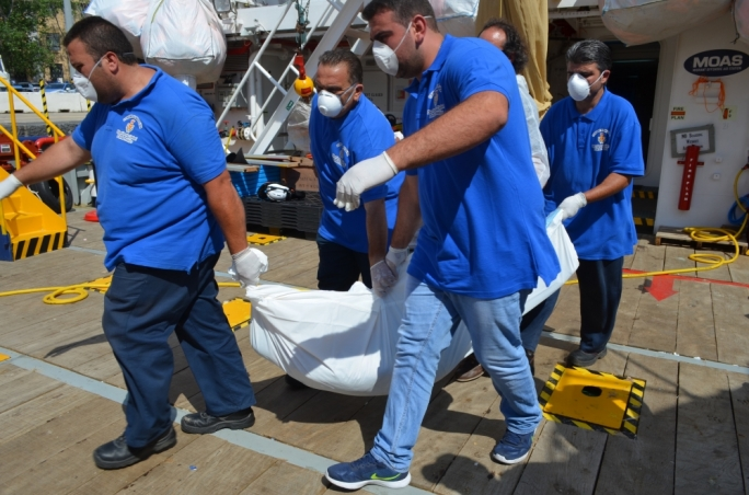 An unidentified migrant who lost his life at sea is removed from the Phoenix vessel operated by MOAS. Photo: Miriam Dalli