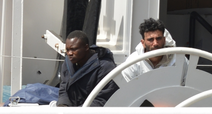 Smuggler Mohammed Ali Malek (right) sitting in a white boiler suit next to a migrant as 24 bodies are transferred onto hearses in Malta. (Photo: Ray Attard)