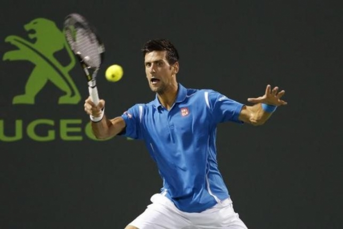 Novak Djokovic hits a forehand against Kyle Edmund (not pictured) during day four of the Miami Open at Crandon Park Tennis Center. Djokovic won 6-3, 6-3.