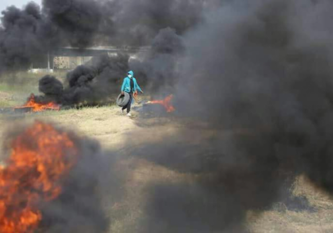 Palestinian protester burning tires