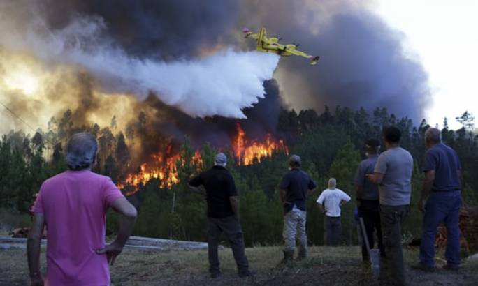 People watch a firefighting plane drop water to stop a raging forest blaze reaching their houses near Mação, central Portugal