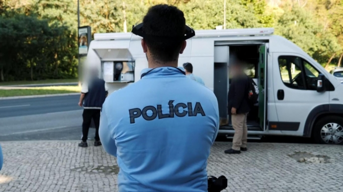 A Portuguese police officer supervises the dispensation of heroin substitute methadone from a takeaway van