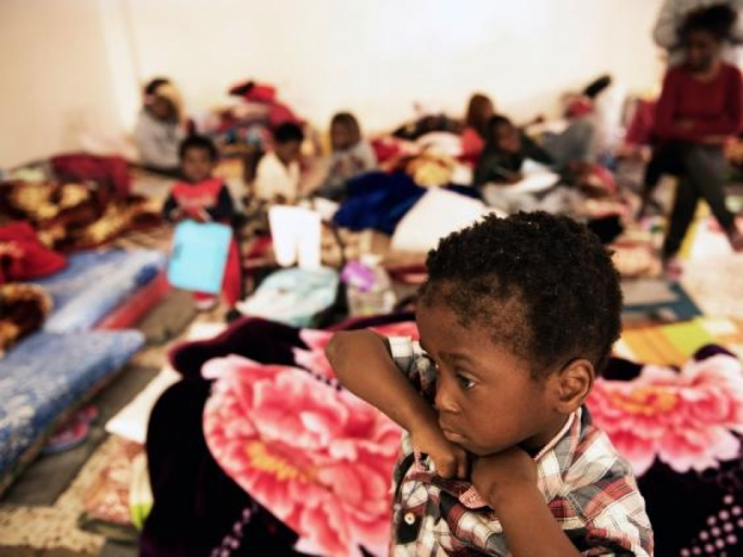 A child stands in a room where women and children sleep on old mattresses laid on the floor at a detention centre, in Libya (Photo: UNICEF)
