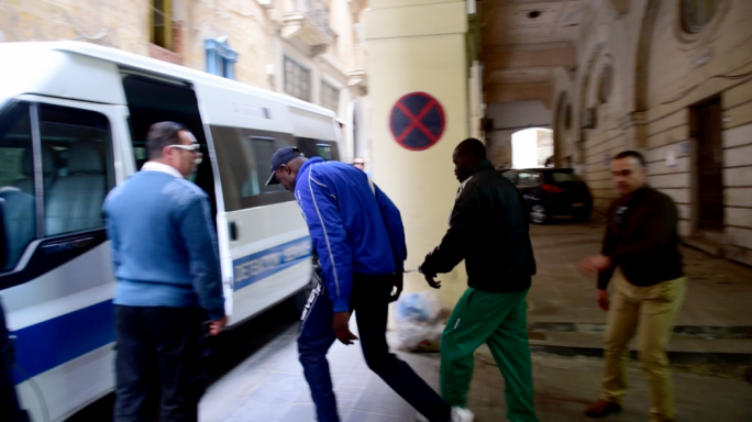 Criminalised: Malian migrants now slated for deportation after years of being tolerated in the country are escorted out of court and into a prison van