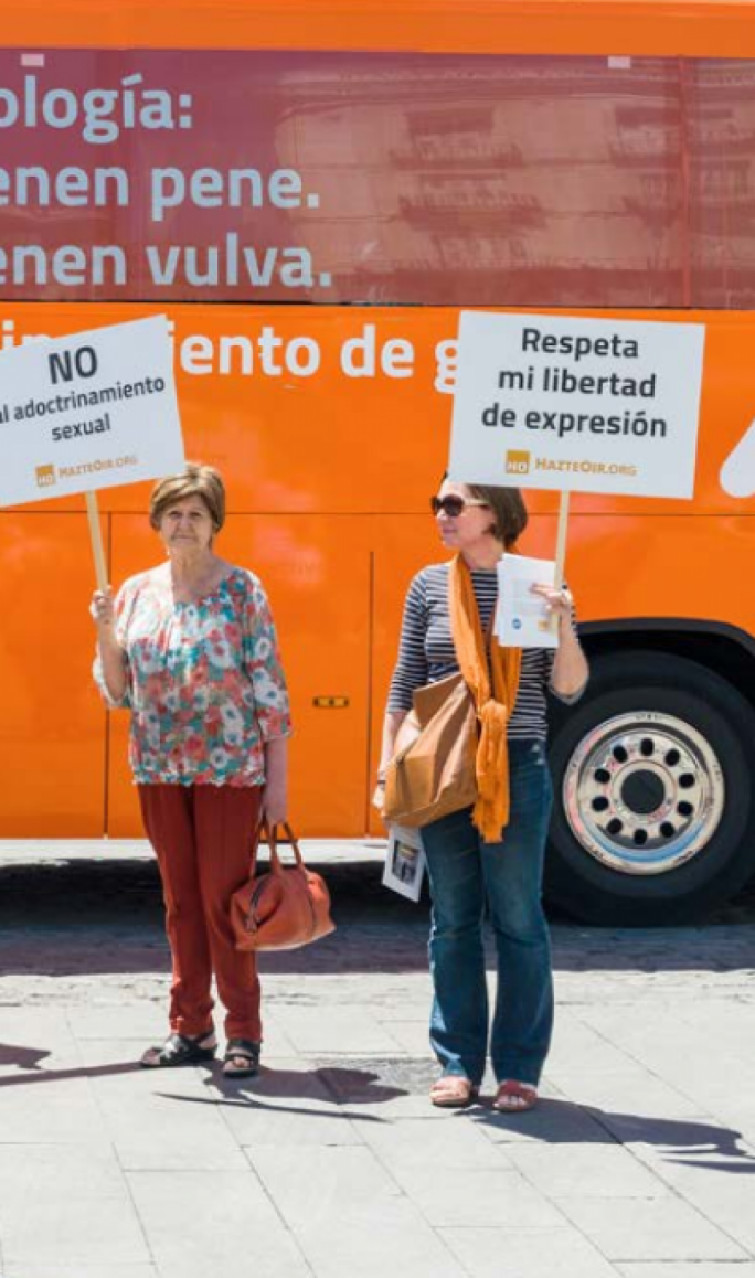 Protestors in Madrid, Spain in 2017; the 'anti-transgender bus' has written on the side: Boys have penises, girls have vulvas, say no to  gender indoctrination