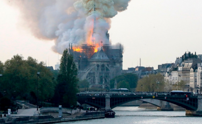 Smokes and flames rise from the landmark Notre Dame Cathedral in central Paris