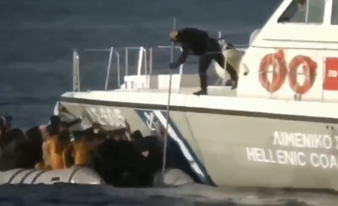 In the video a coastguard officer aboard a large dinging is seen waving his arms at the boat full of migrants before prodding them with a large stick