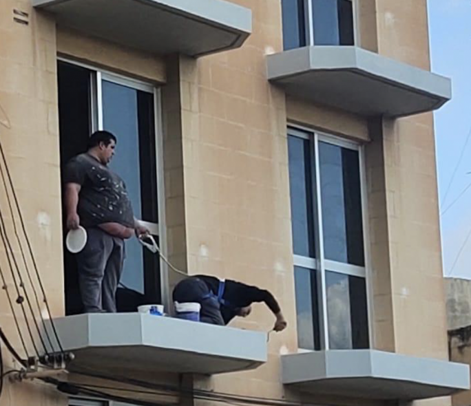 A photo did the rounds on social media of a worker wearing a strap attached to a safety harness worn by another worker while working on the edge of an unshielded gallery