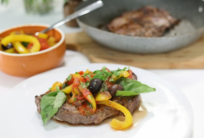 Grilled rib-eye steak with tomato, sweet peppers and anchovies