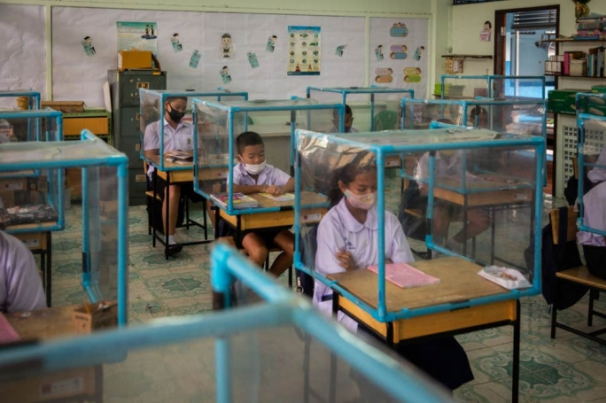 School pupils in Thailand are playing and studying in makeshift plastic cubicles to comply with strict social distancing measures