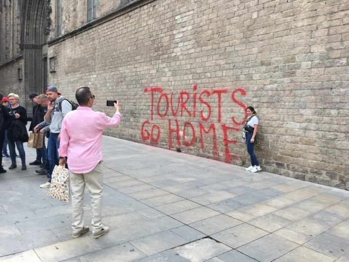 A graffito in Barcelona, where residents complain of the effect that over-tourism and badly behaved tourists have on the city