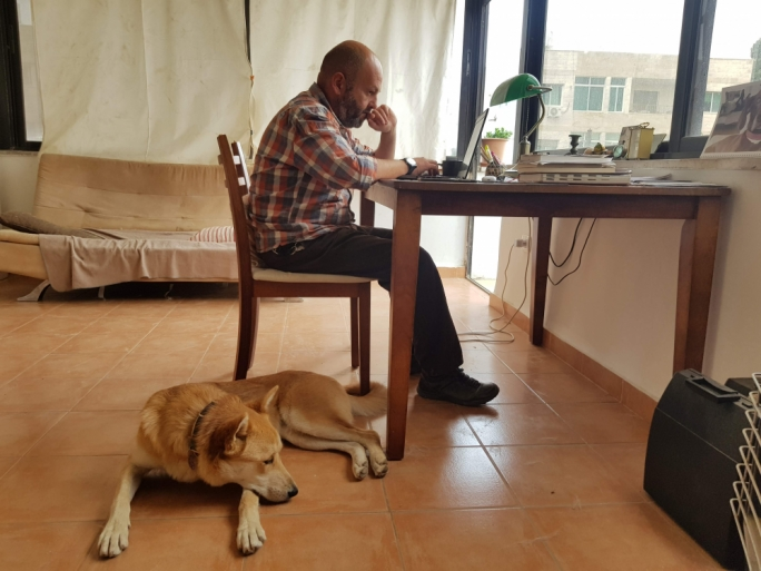 Karl Schembri at his writing desk, while his canine companion Mitti keeps him company Photo by Simine Alam