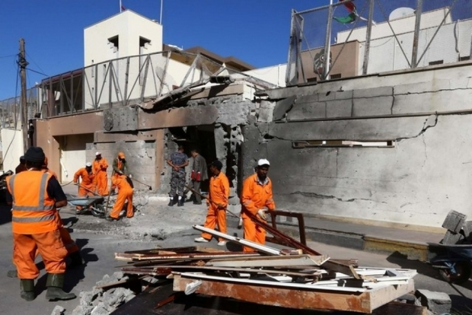 Workers clear the damage outside the UAE embassy building that was targeted by a car bomb in Tripoli, Libya