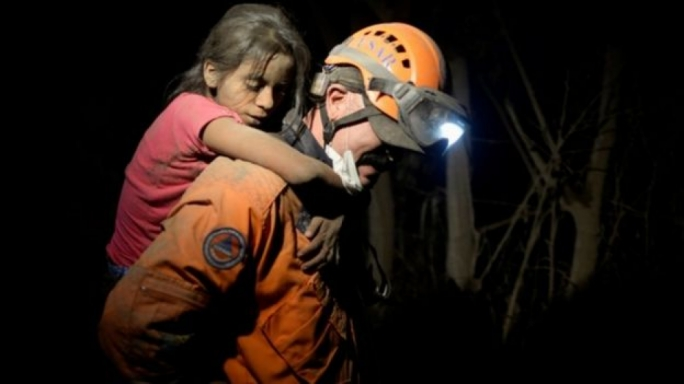 A firefighter carries a child during evacuation. (Photo:Reuters)