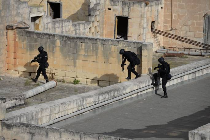 Armed police searching the properties in Marsa