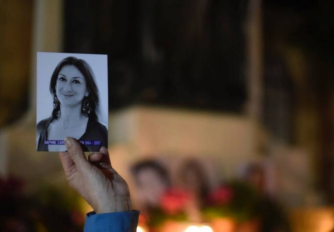A demonstrator holds up a photo of Daphne Caruana Galizia at a vigil held in February 2018