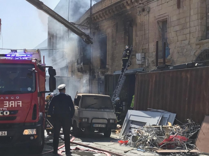 Fire fighters are using cameras to try to locate where the dogs which are caught inside the warehouse are