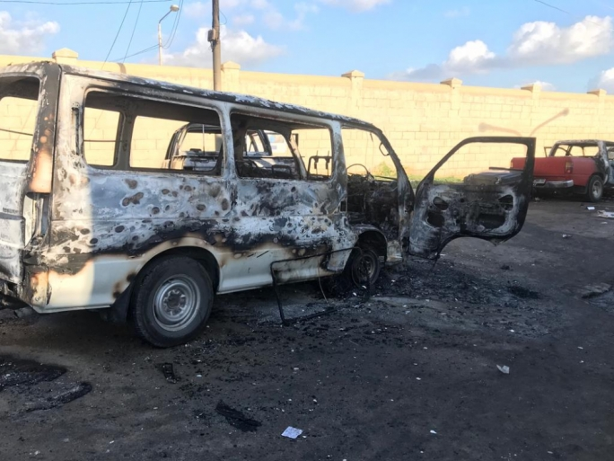 A van, one of five vehicles burnt during the riot